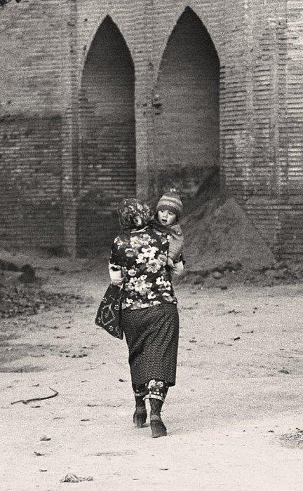 Женщина, несущая маленького ребенка. СССР, Узбекистан, Бухара, 1984 год.