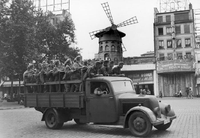 Немецкие солдаты, оккупировавшие Париж, проезжают мимо «Мулен Руж».