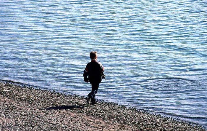 Мальчик, бросающий камни на берегу Ангары. СССР, Иркутск, 1988 год.