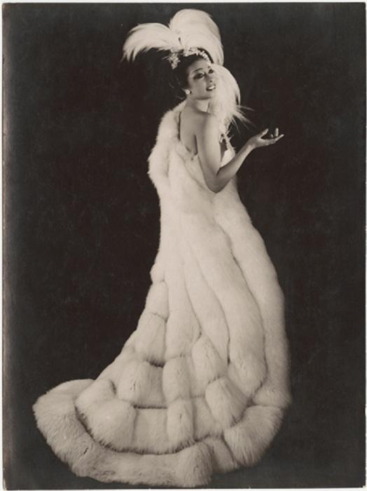 Темнокожая женщина в роскошном меховом манто на фотографии начала XX века.