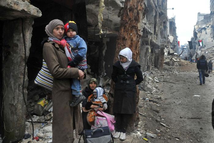 Мирные жители с вещами на развалинах осажденного лагеря беженцев Ярмук. Сирия, Южная окраина сирийской столицы Дамаск. 4 февраля 2014 года.