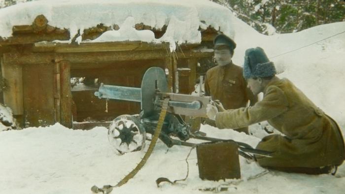 Пулеметчик перед заснеженным бункером.