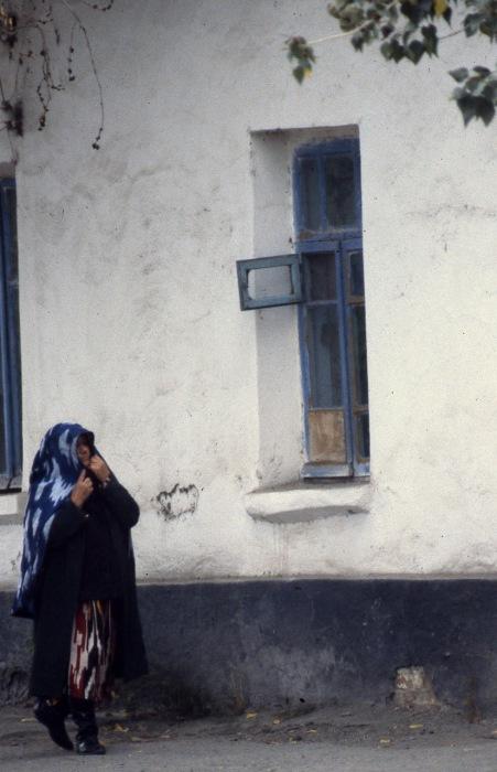 Старуха, идущая рядом с глиняным домом. СССР, Узбекистан, Самарканд, 1984 год.
