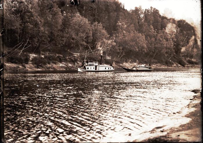 Паровой катер Сибиряк буксирующий каяк по реке.