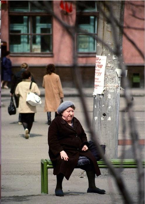 Женщина, сидящая на лавочке в ожидании автобуса. СССР, Иркутск, 1988 год.