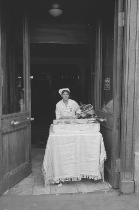 Женщина, продающая пекарские изделия у входа в здание. СССР, Москва, 1961 год.