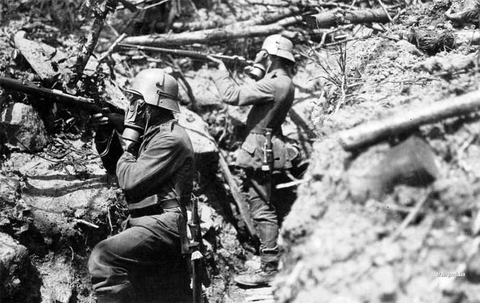 Немецкие солдаты в противогазах и защитных касках.