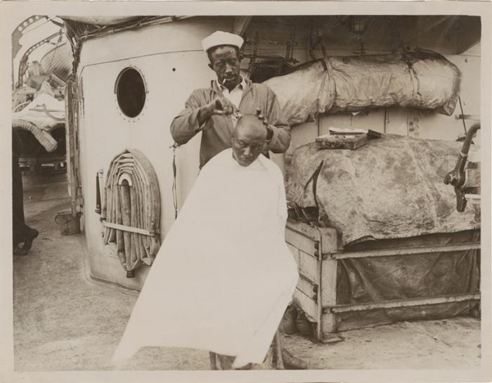 Афроамериканец бреет голову товарищу. Фотография начала XX века.
