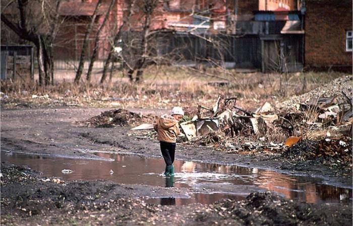 Ребенок, стоящий в луже во дворе домов между улицами Фурье и Чехова. СССР, Иркутск, 1988 год.