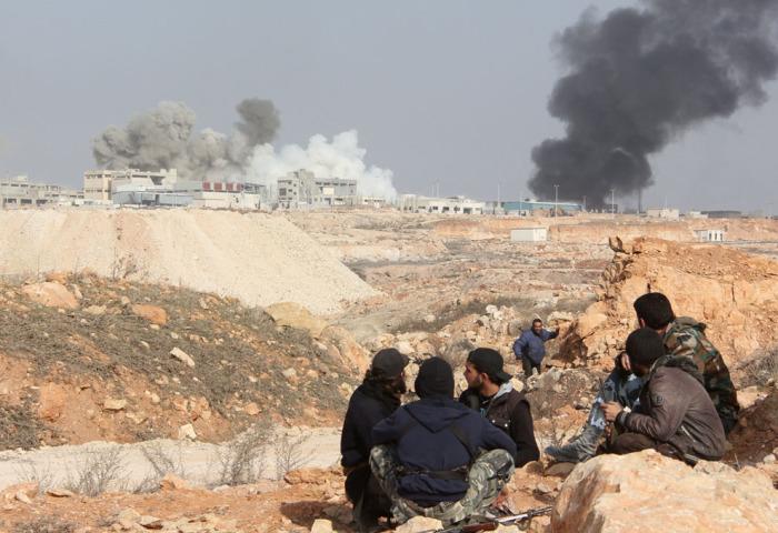 Боевики Свободной Сирийской армии на фоне горящий коммуникаций на окраине сирийского города Алеппо.