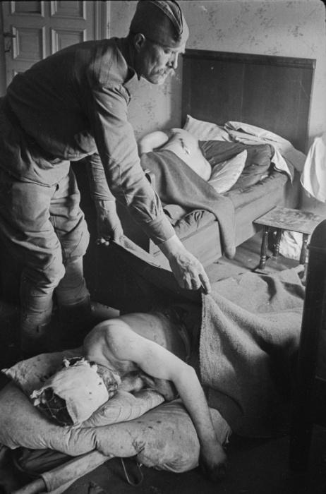 Санитар укрывает одеялом раненого красноармейца в госпитале в Германии.