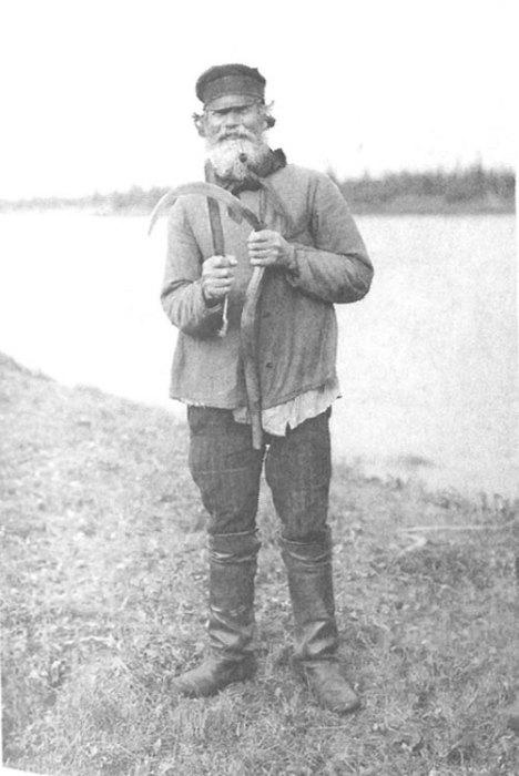 Старик косарь точит косу перед жатвой. Архангельская губерния, Онежский уезд, деревня Порог, 1910 год.