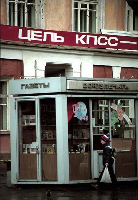 Школьник, идущий вдоль газетного киоска на улице Ленина. СССР, Иркутск, 1988 год.