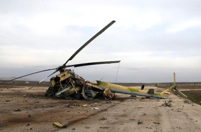 Обломки сбитого вертолёта сирийской армии на взлётно-посадочной полосе в окраине города Алеппо.