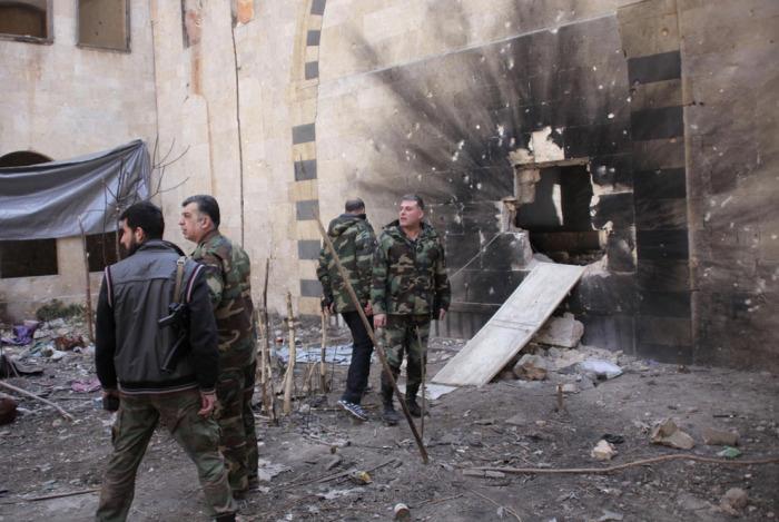 Войска, верные президенту Сирии Башару аль-Асаду возле проломленной от взрыва стены. Старый городе Алеппо, 11 февраля 2014 года.