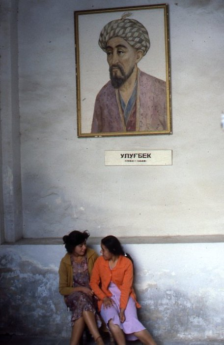 Две девочки, сидящие под портретом Улугбека. СССР, Узбекистан, Самарканд, 1984 год.