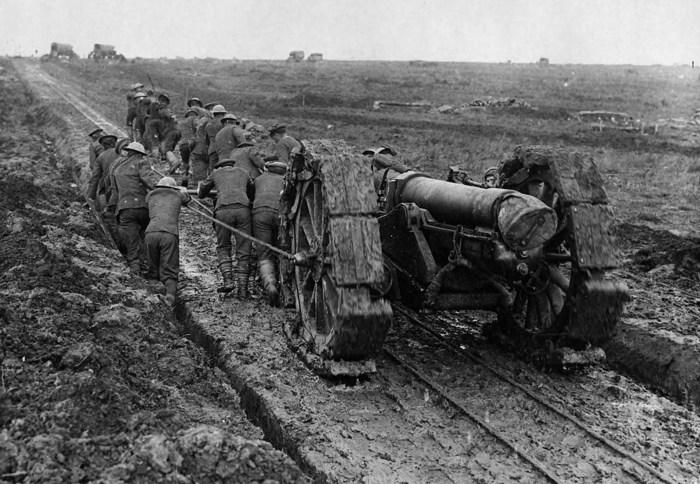 Солдаты тянут тяжёлое артиллерийское орудие по грязи.