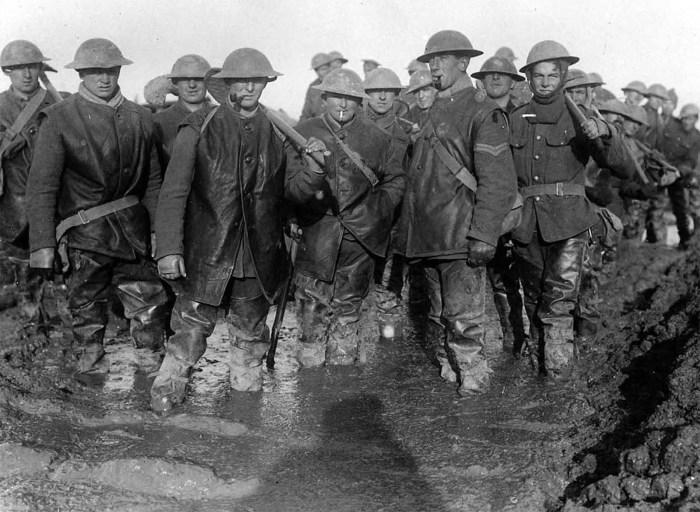 Британские солдаты стоят по колено в грязи на французских позициях.