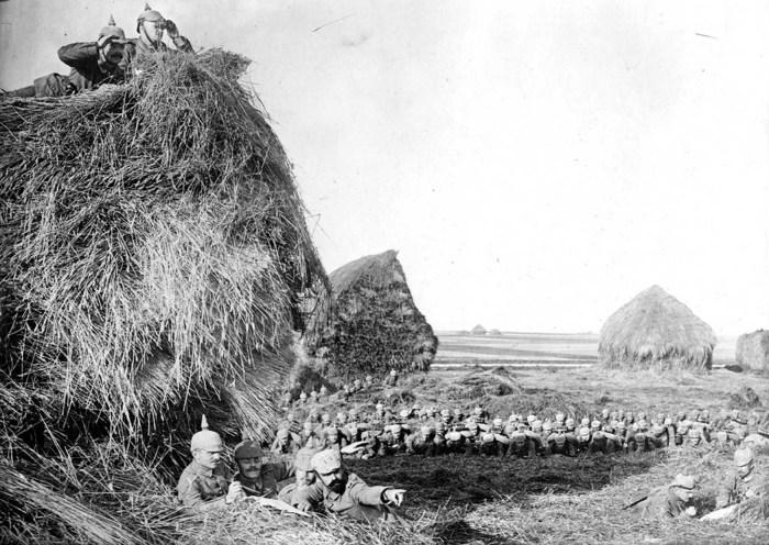 Немецкие солдаты производят рекогносцировку, укрывшись за большими стогами.