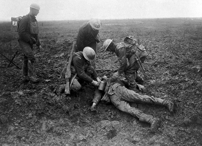 Канадские солдаты досматривают убитого немецкого солдата.