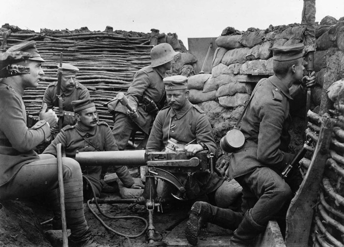 Шестеро немецких солдат позируют в траншее с пулеметом.
