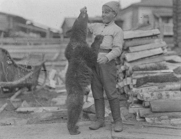 Мальчик, кормящий медвежонка-талисмана батальона Лапинского в 1919 году.