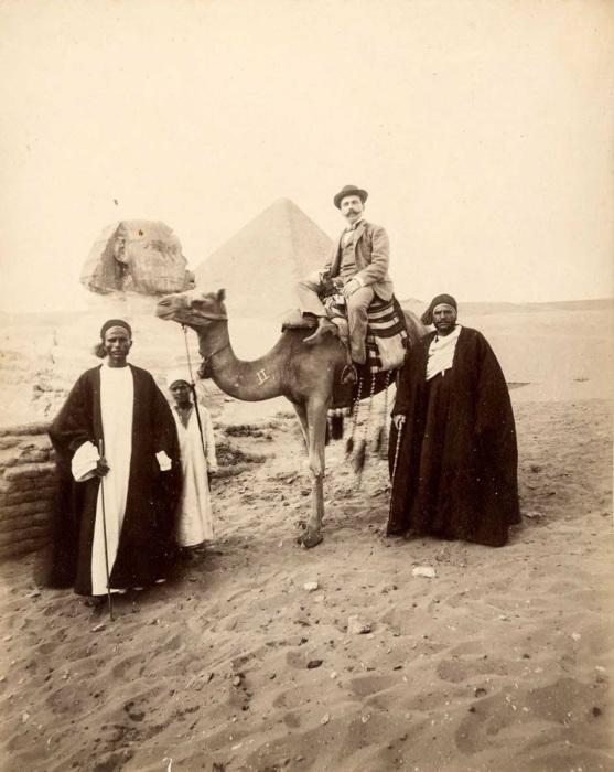 Турист и гиды с верблюдом.