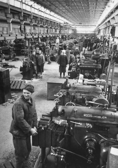 Рабочие работающие на заводских станках.