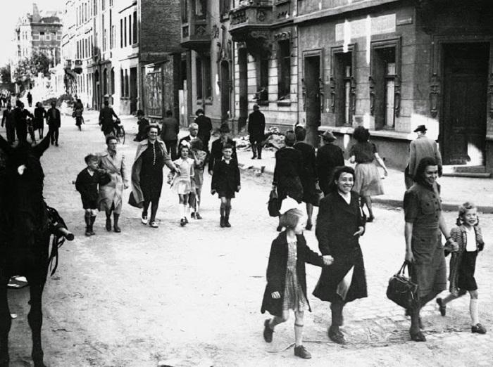 Родители ведут своих детей в первую школу, открытую после войны американским правительством.