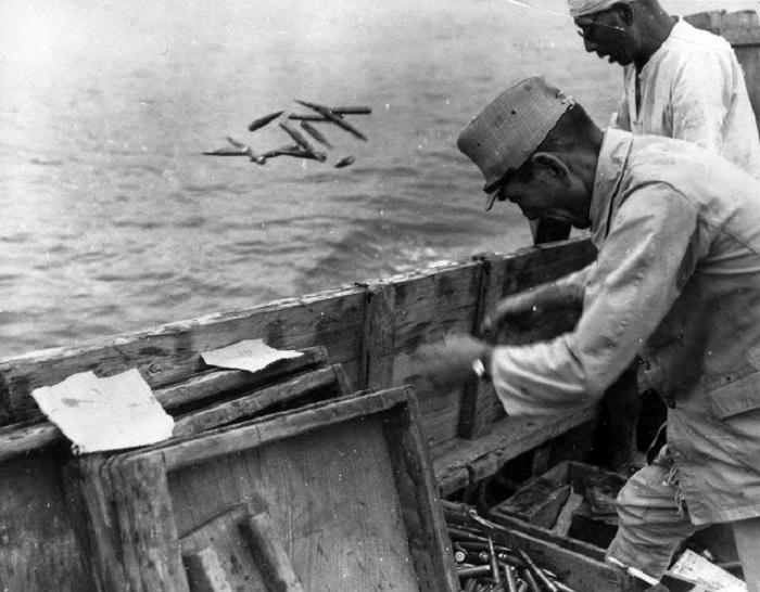 Солдаты выбрасывают в море японские боеприпасы.