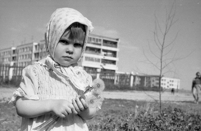 Портретная фотография девочки с одуванчиками.