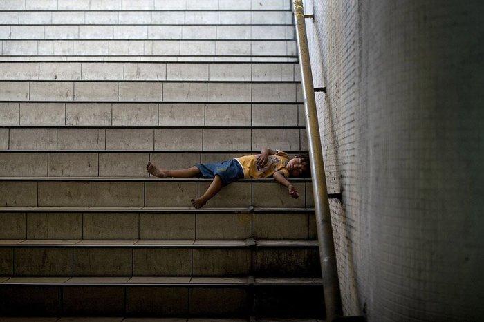 Ребенок спит на ступеньках подземного перехода.