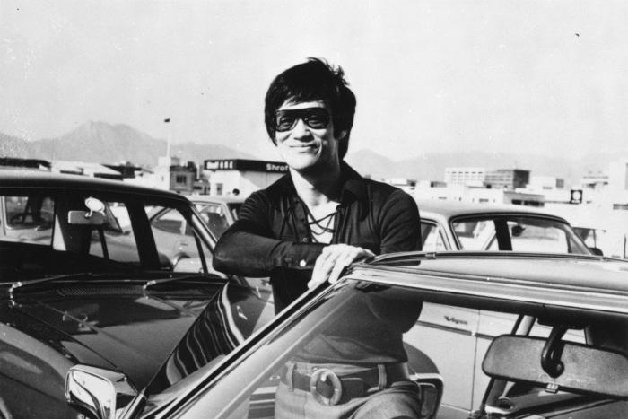 Жизнерадостный Брюс Ли возле своей машины на автостоянке неподалеку от киностудии.