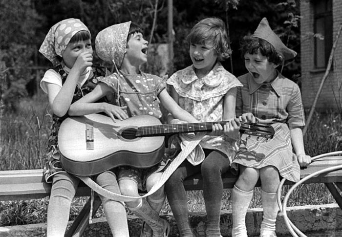 Дівчата, які відіграють на гітарі в шкільному дворі.