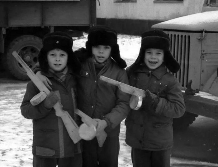 Підлітки, які грають у войнушки з дерев'яними автоматами.
