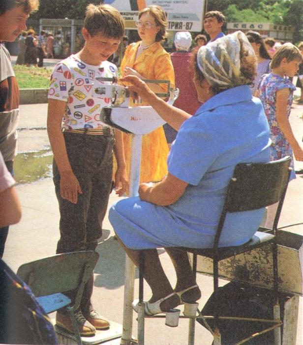 Жінка, яка вимірює вагу підлітку на вулиці.