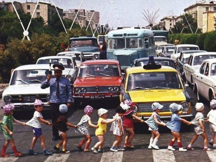 Міліціонер зупинив рух для безпечного переходу дітей через дорогу.