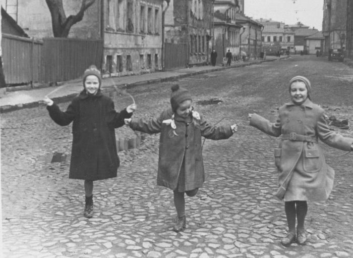 Дівчатка, стрибають на скакалці на одній з вулиць.