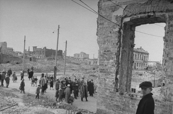 Журналисты разглядывающие разрушенные здания в центре города.