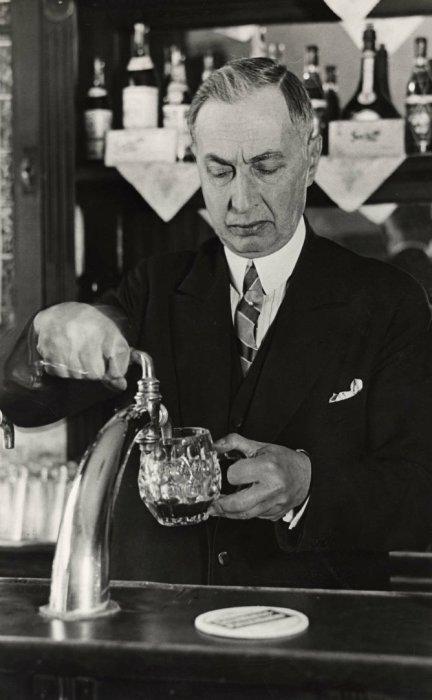 Самый известный в России комический актер оперетты Александр Полонский, в эмиграции работающий за барной стойкой в небольшом русском кафе в Берлине. Германия, 1930 год.