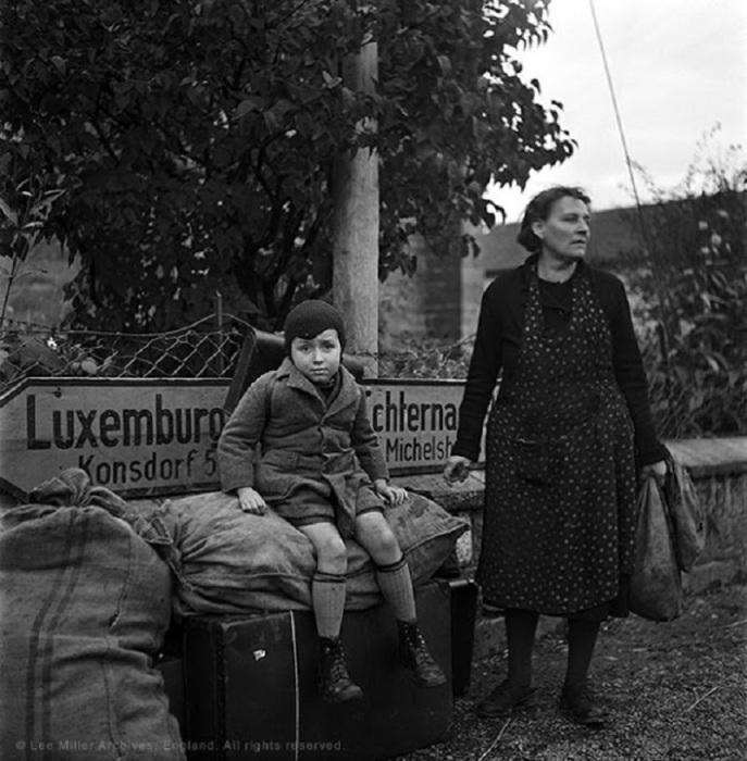 Уставшая от длительной дороги мать с сыном ждут на перекрестке транспорт. Люксембург, 1945 год.
