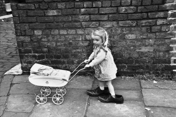 Девочка с коляской в мужских туфлях. Англия, Манчестер, 1966 год.