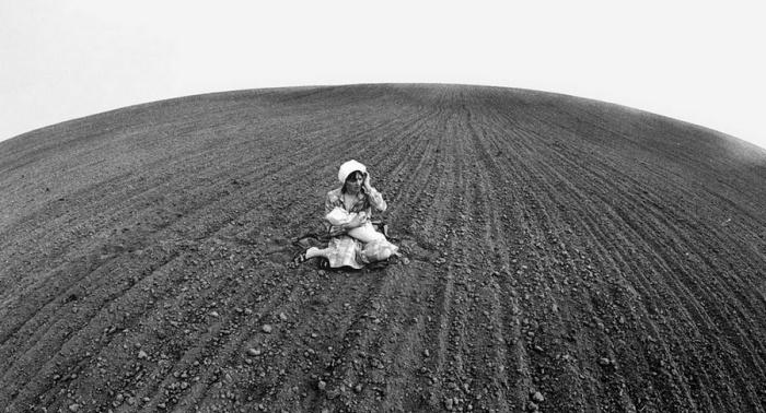 Женщина с ребенком на руках в поле. СССР, 1987 год.