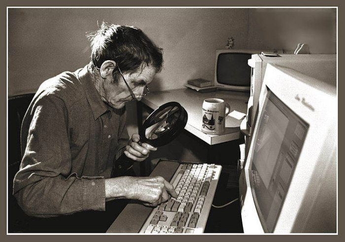 Пожилой мужчина, набирающий текст на клавиатуре.