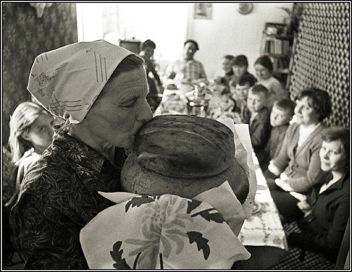 Женщина, целующая свежеиспеченный хлеб перед подачей его на стол.