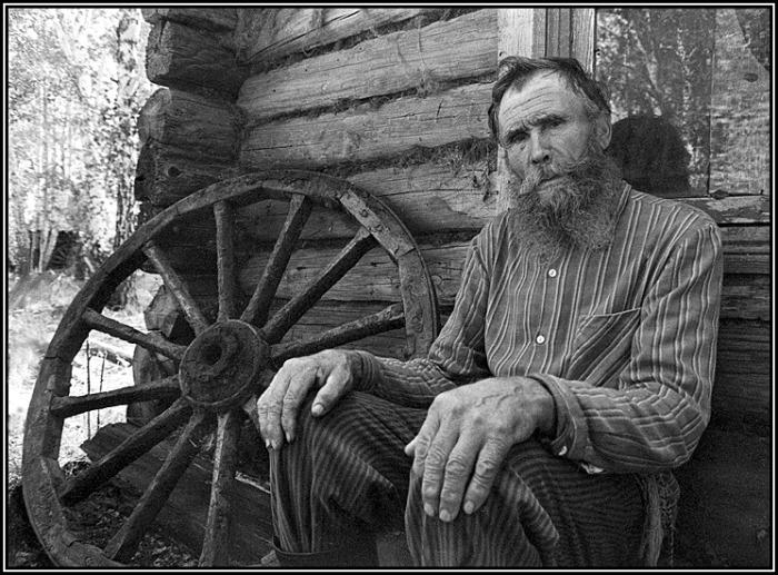 Пожилой мужчина, сидящий возле своего дома.