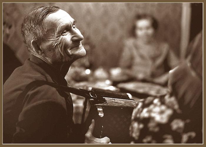 Пожилой мужчина, играющий на тальянке в домашнем кругу.