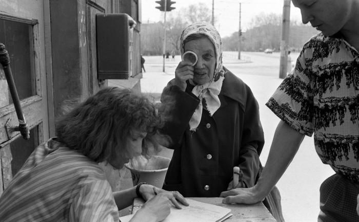 Бабушка с лупой на пункте сбора подписей за Бориса Ельцина, 1991 год.