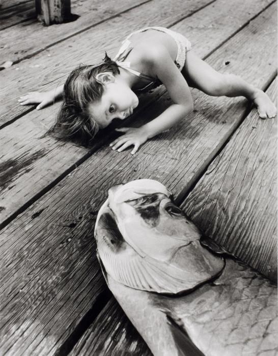 Заглядывает в рот большой рыбе, которую только что поймал папа. Флорида, США, 1956 год.
