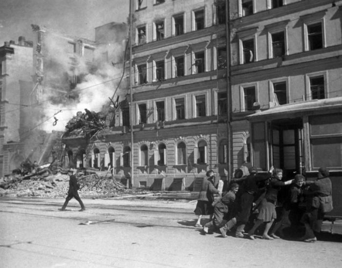 Жители блокадного Ленинграда передвигают трамвайный вагон.